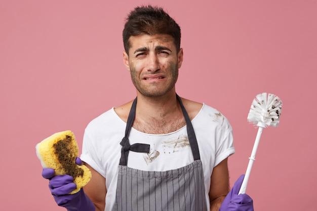 Beklemtoonde trieste knappe student die bij roze muur staat met toiletborstel en spons jankend omdat hij huishoudelijk werk haat maar moet schoonmaken Gratis Foto