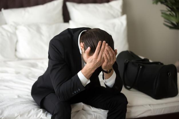 Beklemtoonde verstoorde zakenmanzitting op bed, die hoofdpijn hebben. Gratis Foto