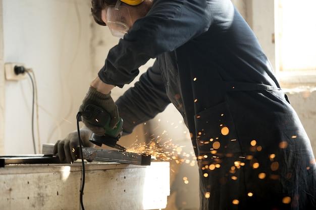 Bekwaam werkman slijpmetaal profiel pijp met veel vonken Gratis Foto