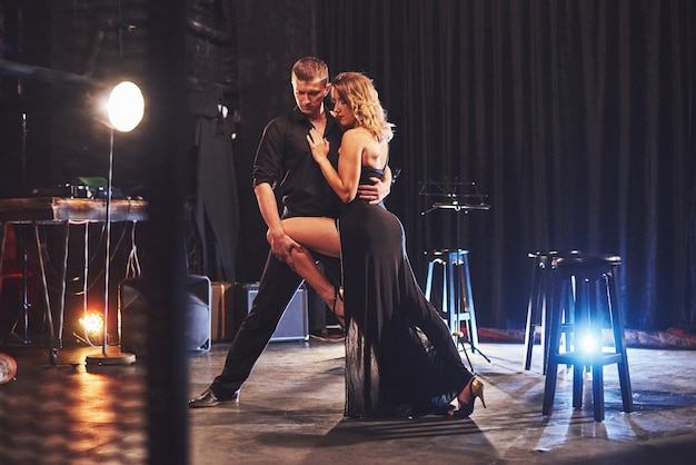 Bekwame dansers die in een donkere kamer onder licht presteren. Gratis Foto