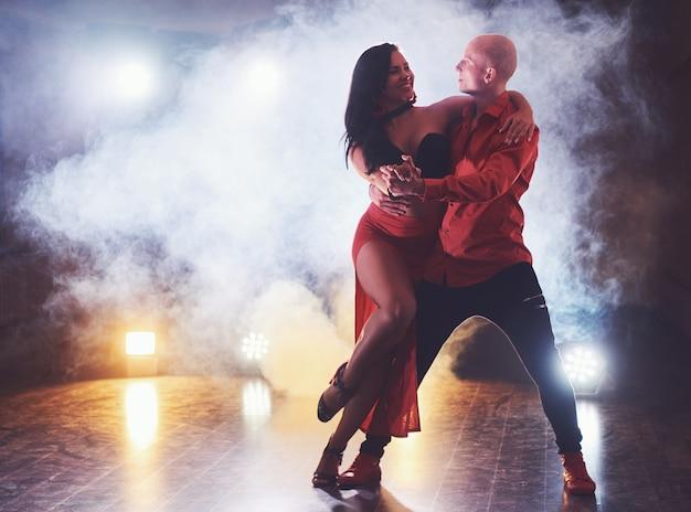 Bekwame dansers die optreden in de donkere kamer onder het concertlicht en rook. sensueel paar dat een artistieke en emotionele eigentijdse dans uitvoert Gratis Foto