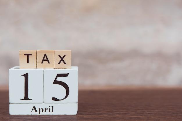Belasting met 15 april. alfabet en kalender houten blok kubus met nummer op tafel donkere plank houten met kopie ruimte Premium Foto
