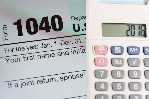 Belastingformulier op tablet scherm en rekenmachine Gratis Foto