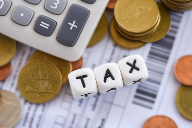 Belastingsconcept en calculator gestapelde muntstukken op het document van de factuurrekening voor tijdbelasting die betaalde schuldbetaling bij bureau bedrijfsfinanciën vullen Premium Foto