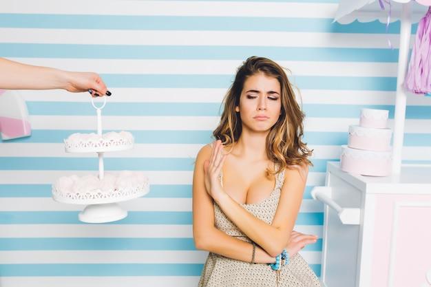 Beledigde krullende vrouw in mooie jurk weigert marschmellow te eten, staande op gestreepte muur. portret van ongelukkig modieus meisje dat geen zoet dessert wegens dieet wil. Gratis Foto