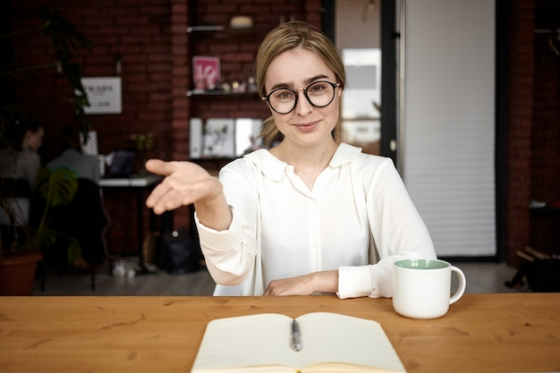 Beleefd personeelsmanager in brillen zittend aan haar bureau, hand uitstrekkend naar de camera, open voor samenwerking, maakt een welkomstbord en zegt: neem plaats. vriendelijke zakenvrouw begroeting partner Gratis Foto