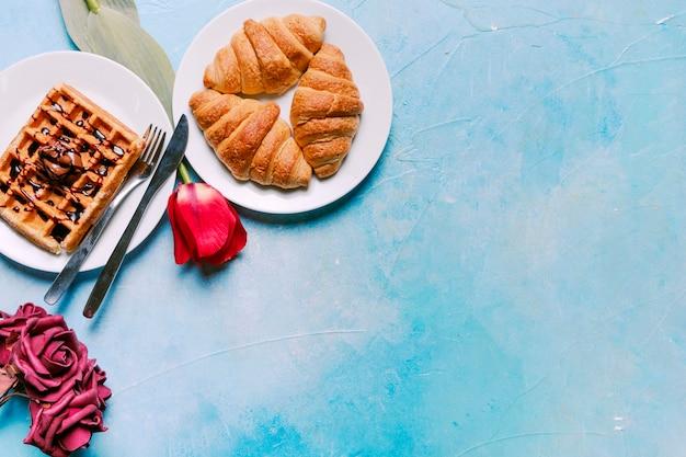 Belgische wafel met croissants en bloemen Gratis Foto