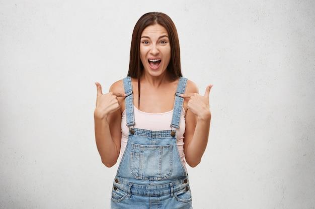 Ben je over mij aan het praten? binnenopname van emotionele, boze, verontwaardigde tienervrouw die hardop schreeuwt, met haar vingers naar zichzelf wijst terwijl ze met haar vriendje aan het kibbelen is, geïrriteerd en geïrriteerd Gratis Foto