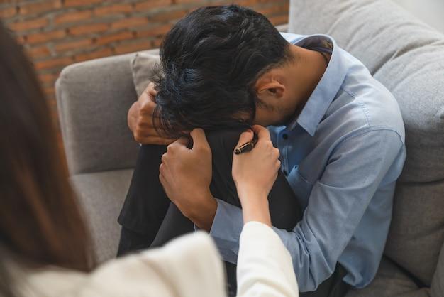 Benadrukt aziatische jongeman patiënt leven probleem zit op de bank met handen met zijn hoofd terwijl vrouw psychiater probeert hem te troosten Premium Foto