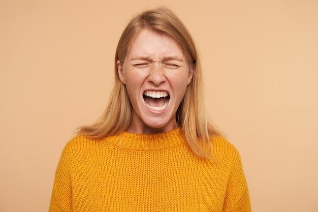 Benadrukt jonge langharige roodharige vrouw met casual kapsel die haar ogen gesloten houdt terwijl ze haar gezicht dwars grimassen, geïsoleerd op beige Gratis Foto