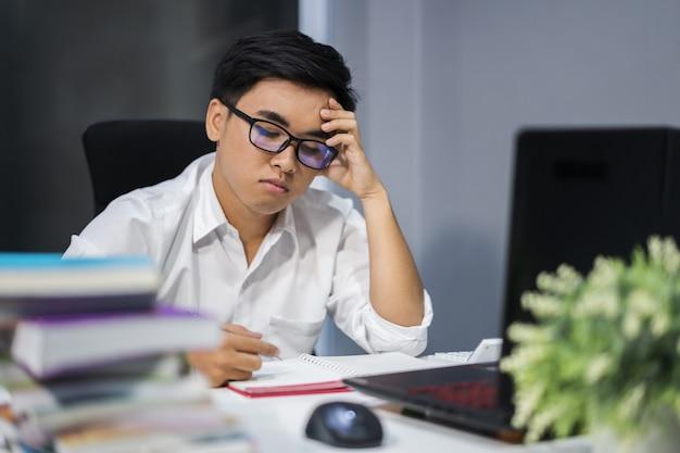 Benadrukt man studeert met boek en laptop Premium Foto