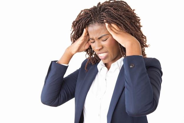 Benadrukt ongelukkige vrouwelijke werknemer die aan hoofdpijn lijdt Gratis Foto