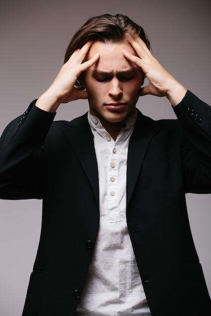 Benadrukt zakenman met hoofdpijn geïsoleerd op een grijze muur Gratis Foto