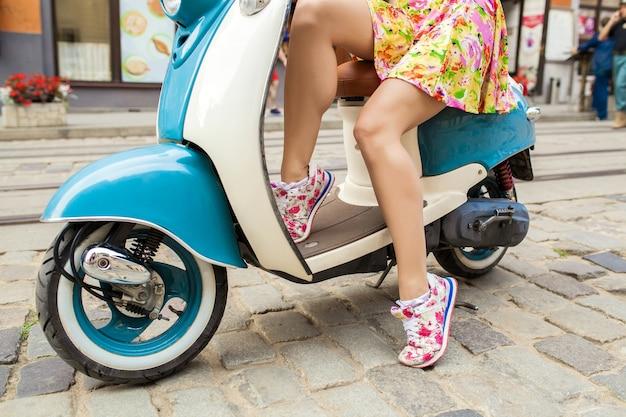 Benen in sneakers van jonge mooie vrouw rijden op motor stad straat Gratis Foto