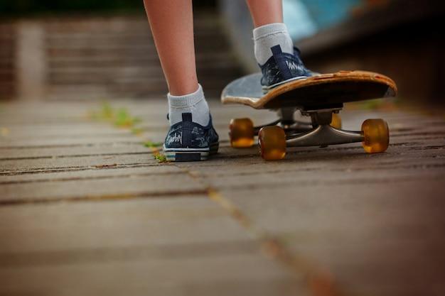 Benen op skateboard dichte omhooggaand op de straat in zonnige dag Premium Foto