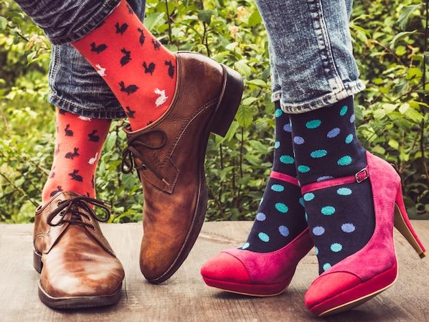 Benen van een jong stel in stijlvolle schoenen, heldere, kleurrijke sokken Premium Foto