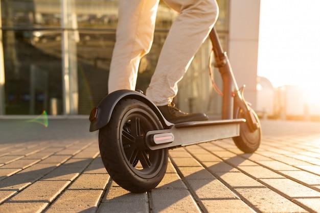 Benen van een man staande op e-scooter geparkeerd op stoep Premium Foto