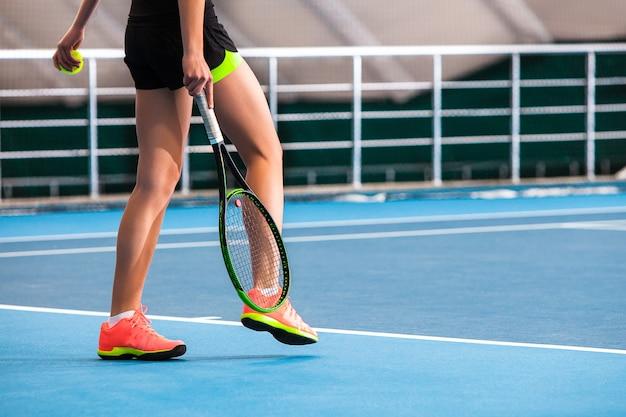 Benen van jong meisje in een gesloten tennisbaan met bal en racket Gratis Foto