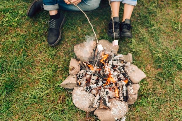 Benen van paar dichtbij vuur die marshmallows roosteren. Premium Foto