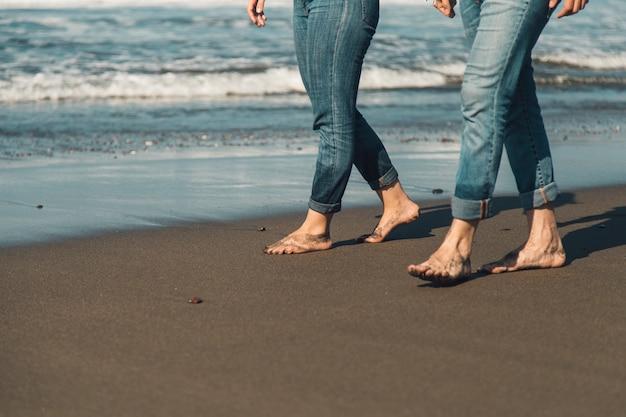 Benen van paar die langs overzees wandelen Gratis Foto