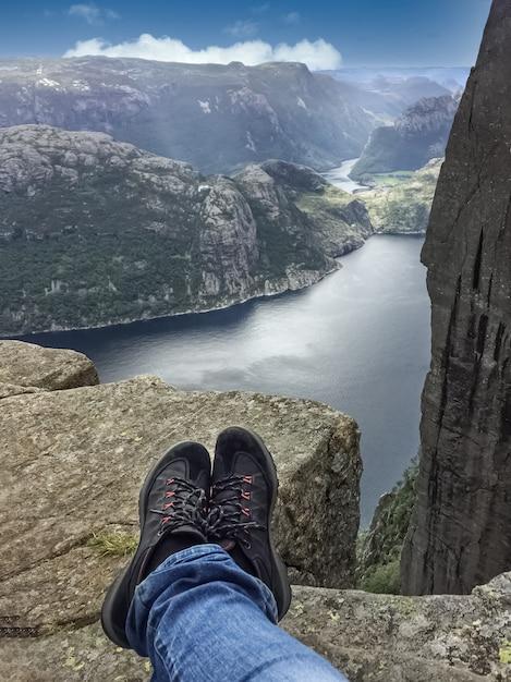 Benen van reiziger zittend op hoge berg klif, genieten van landschap van noorse fjorden vanaf bergtop Premium Foto