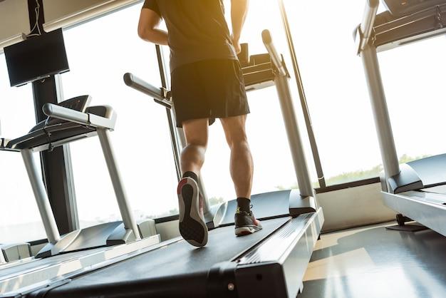 Benen van sportman die op tredmolen in fitness gymnastiekcentrum lopen. sport en een gezonde levensstijl concept. Premium Foto
