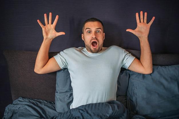 Benieuwd jonge man zit op bed en kijkt rechtdoor camera. hij houdt zijn handen omhoog. guy is bang en bang. Premium Foto
