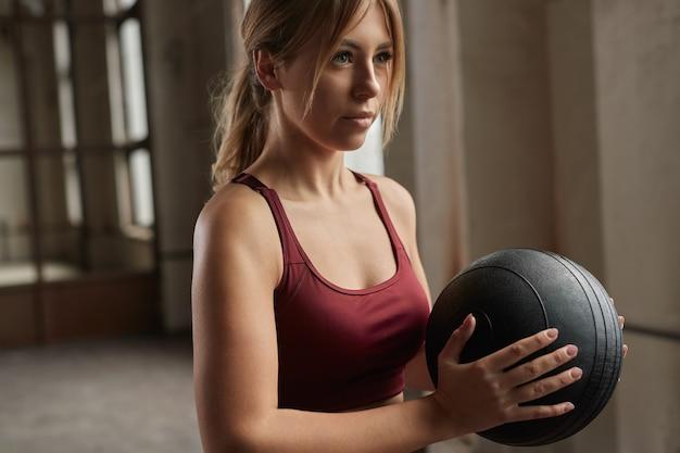Bepaalde jonge fit vrouw met zware medicijnbal in handen oefening voorbereiden tijdens intensieve functionele training in de sportschool Premium Foto
