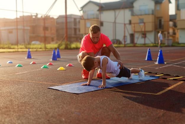 Bepalende jonge voetbalcoach die jongetje leert hoe hij push-ups moet doen. Premium Foto