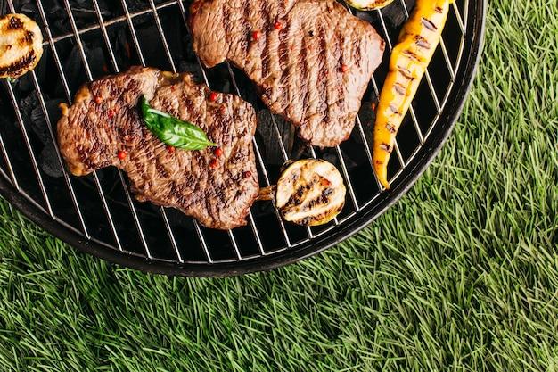 Bereiding van gegrilde biefstuk en groente op barbecue over grasmat Gratis Foto