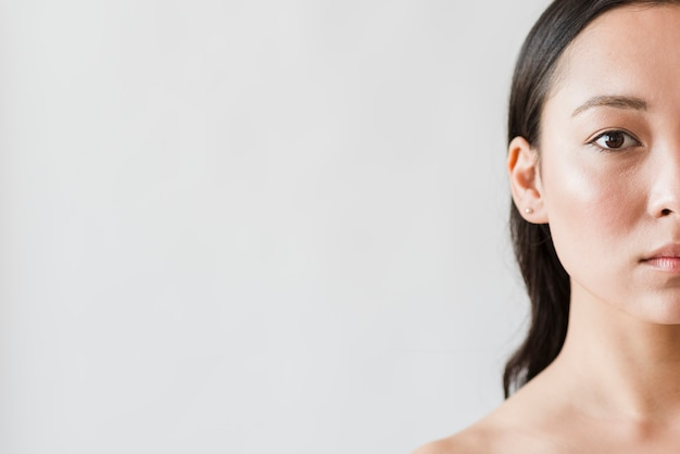 Bereik aziatische vrouw die camera bekijkt Gratis Foto