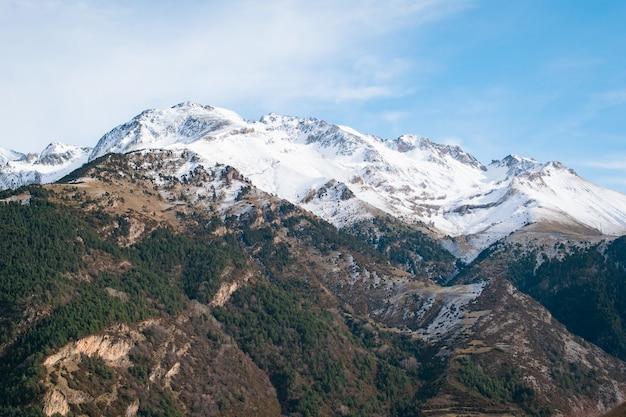 Bereik van hoge rotsachtige bergen bedekt met sneeuw onder de bewolkte hemel Gratis Foto