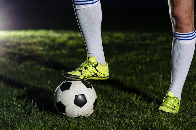 Bereikbenen die op voetbalbal stappen Gratis Foto