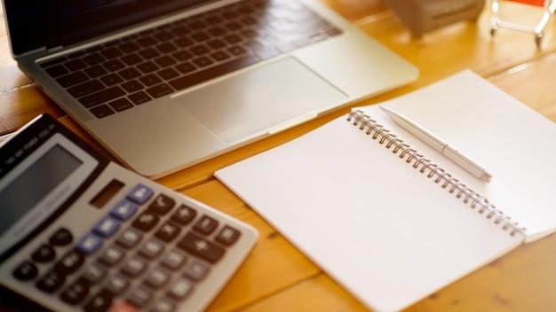 Bereken de kosten met behulp van de rekenmachine en laptop. kosten berekening concept Premium Foto