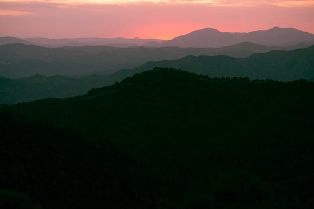 Bergen in het zwart met roze lucht Gratis Foto