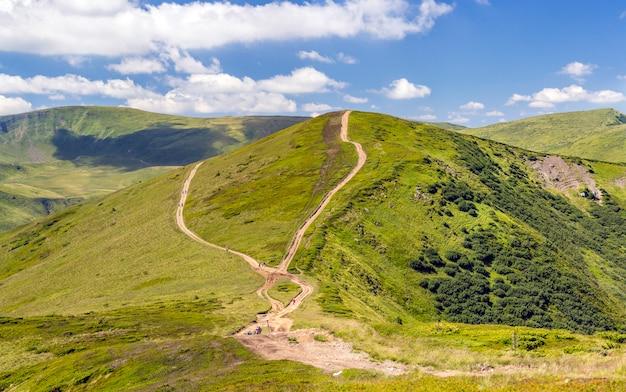 Bergketen met onverharde weg en wandelaars. karpatische bergen in oekraïne in de zomer Premium Foto