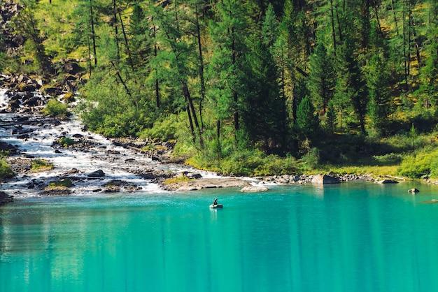 Bergkreek stroomt in meer. bekijk boven visser in boot op azuurblauwe water. prachtig bos in zonlicht. grote keien in beek. sfeervol mooi landschap van hooglandaard in zonnige dag. Premium Foto