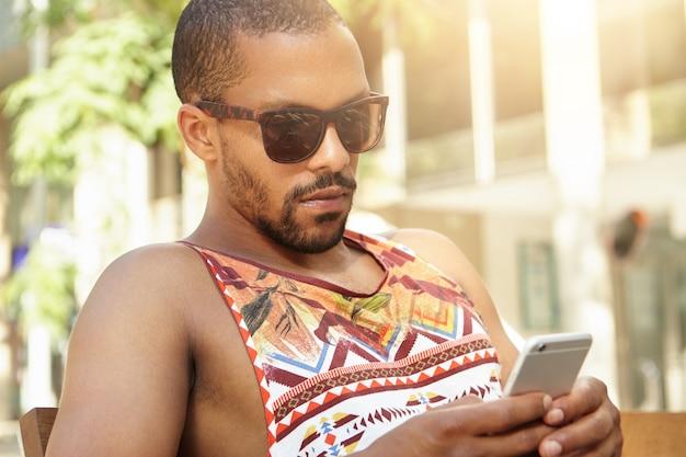 Beroemde trendy afrikaanse blogger in tinten die zich verbergen voor de zomerhitte in het park met behulp van een smartphone voor het delen van zijn nieuwe post via sociale netwerken, en hij ziet er serieus en geconcentreerd uit. zwarte mens die in openlucht texting Gratis Foto