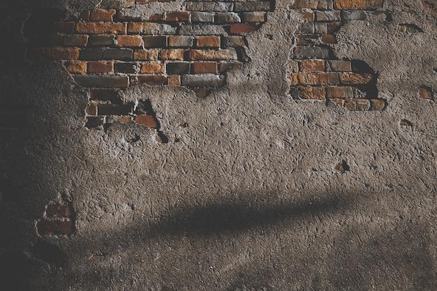 Beschadigde cementmuur met bakstenen Gratis Foto