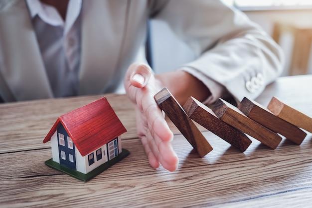 Bescherm het huis tegen omvallen van de houten blokken, verzekering en risicoconcept. Premium Foto