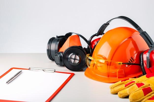 Beschermende bouwvakker, hoofdtelefoons, handschoenen, bril en klembord op grijs oppervlak. bouwveiligheid. Premium Foto