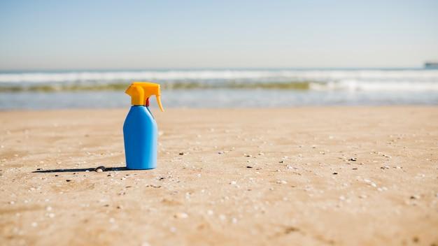 Bescherming tegen de zon en zonnebrand cosmetica fles op zand op het strand Gratis Foto