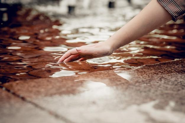 Bescherming van zoet water op aarde. uitdroging. close-up vinger raakt water en waterdruppel aan en creëert natuurlijke en kalme golven, kalm concept. Premium Foto