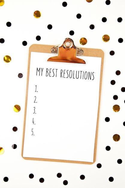 Bespotten met notitieblok en confetti voor nieuwe jaarresoluties Premium Foto