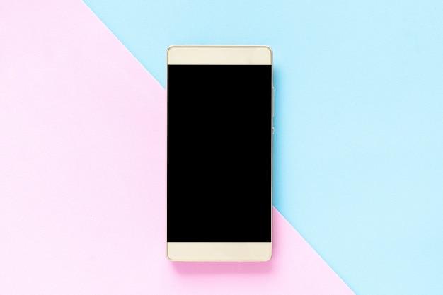 Bespotten smart-phone op een roze en lichtblauwe achtergrondpastelkleur Premium Foto