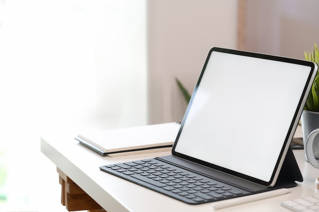 Bespotten van lege scherm tablet met slimme toetsenbord op witte bureau Premium Foto