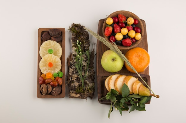 Bessen, fruitmix en kruiden in een houten schaal in het midden Gratis Foto