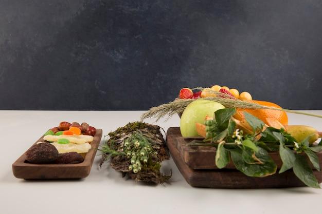 Bessen, fruitmix en kruiden in een houten schotel die op witte ruimte wordt geïsoleerd Gratis Foto