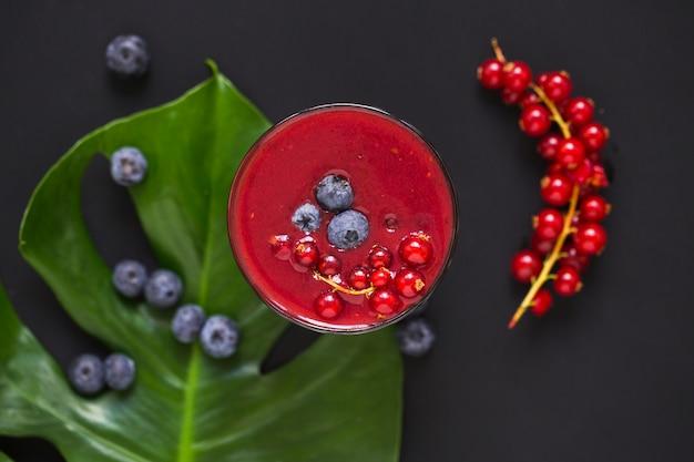 Bessen smoothies op blad tegen zwarte achtergrond Gratis Foto