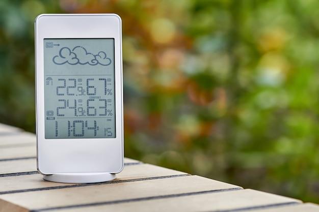 Beste persoonlijke weerstation apparaat met weersomstandigheden binnen en buiten op gebladerte achtergrond. home digitaal weersvoorspellingsconcept met temperatuur en vochtigheid. Premium Foto